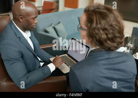 Joven empresario africano trabajando en el portátil mientras está sentado con su colega. Los empresarios reunidos en una cafetería.