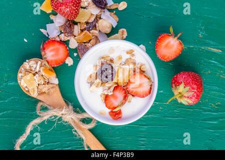 Yogur con cereales, muesli, fresas frescas, plátano y pasas en recipiente sobre fondo de madera