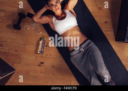 Fotografía cenital de colocar joven acostada en la estera del yoga con sus manos detrás de la cabeza y mirando a la cámara. Determina hembra listo para