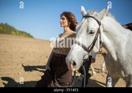 Atractiva chica joven está caminando con su caballo