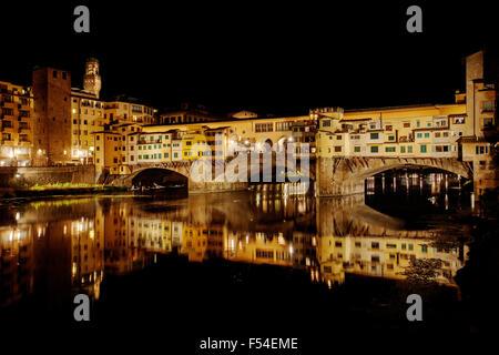 El Ponte Vecchio, el Puente Viejo, Taddeo Gaddi, sobre el río Arno en Florencia, Italia en la noche