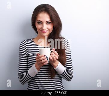 Lindo casual joven mujer sosteniendo en la mano una taza de té y sonriendo sobre fondo azul.