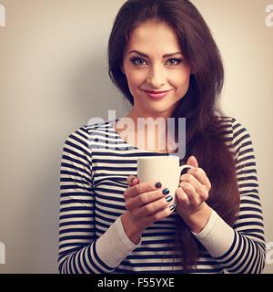 Lindo casual joven mujer sosteniendo en la mano una taza de té. Tonos Vintage retrato. Closeup