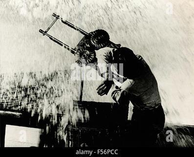 El artillero entre los charcos de agua en un buque de guerra Foto de stock