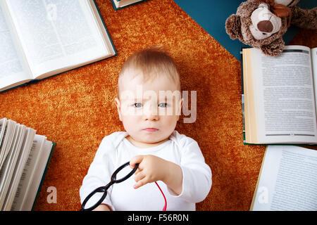 Bebé de Un año de edad con un oso de peluche y spectackles