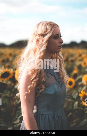 Hermosa mujer joven en un campo de girasol en hora dorada