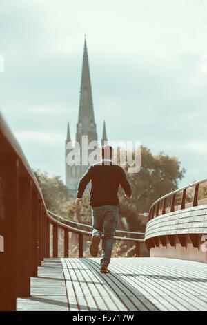 Hombre corriendo a través de puente urbano con la iglesia en el fondo