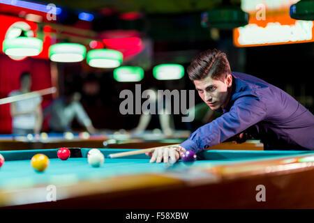Joven apuesto hombre inclinado sobre la mesa mientras juega billar