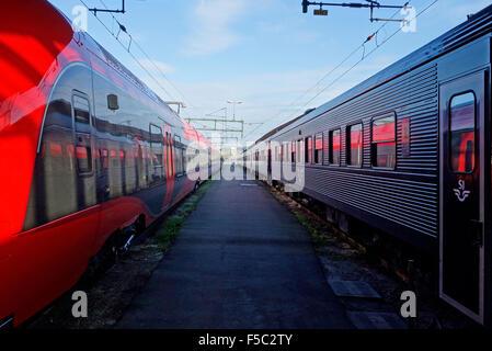 Dos trenes de ferrocarril en cada lado de una plataforma vacía en la estación central de Göthenburg, Suecia