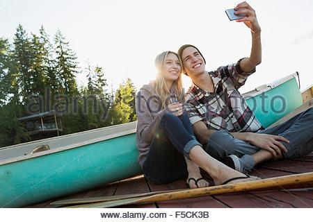 Pareja joven sonriente tomando selfie dock cerca de canoa Foto de stock