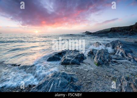 Impresionante puesta de sol sobre la playa rocosa a Trevone bahía cerca de Padstow en Cornwall.