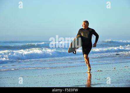 Un varón de mediana edad trotar en el Ocean Edge mantiene una tabla de surf. Suave luz temprano por la mañana lava sobre la deliciosa escena.