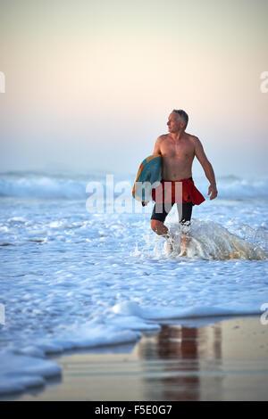Un varón de mediana edad caminando en las olas del océano lavar sosteniendo una tabla de surf. Suave luz temprano por la mañana lava sobre la deliciosa escena.