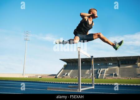 Pista y Campo masculino profesional atleta durante la carrera de obstáculos. Joven atleta saltar por encima de un obstáculo durante el entrenamiento en pista