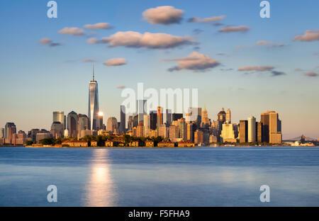 El horizonte de la ciudad de Nueva York, Manhattan. Ellis Island aparece delante de los rascacielos del distrito financiero Foto de stock