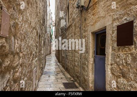 Estrecho, vacío y húmedo callejón o calle peatonal en el casco antiguo de la ciudad de Split, Croacia.