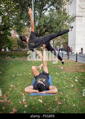 Los hombres no caben dos atléticos acro yoga ejercicios en Washington Square Park, en la Ciudad de Nueva York Foto de stock