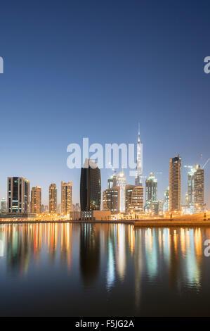 Horizonte de torres se refleja en el arroyo al atardecer en la Bahía de Negocios en Dubai, Emiratos Árabes Unidos Foto de stock