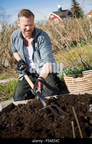 Suecia, Estocolmo, Alvsjo, Hombre trabajando en el jardín