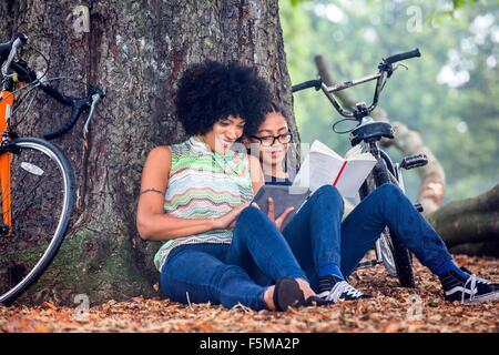 Mujer madura e hijo sentarse contra el árbol del parque libro de lectura y tableta digital