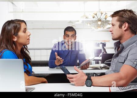 Un pequeño grupo de gente que tiene negocios, colegas masculinos y femeninos habiendo desacuerdo