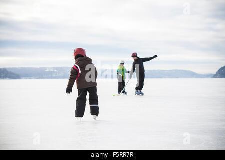 Suecia, Vastergotland, Lerum, lago Aspen, Mamá juega el hockey sobre hielo con sus dos hijos (6-7, 8-9) en el lago Foto de stock