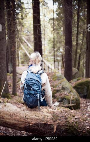 Suecia, Vastergotland, Lerum, hembra backpacker sentado en el tronco del árbol caído en el bosque