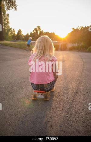 Suecia, Smaland, Anderstorp, Retrato de niña (8-9) sentados en rojo shortboard en calle
