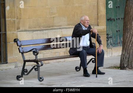 Anciano sentado en un banco en Ubeda España Foto de stock