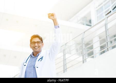 Exitoso médico indio asiático con el brazo celebrando su victoria, el edificio del hospital como fondo.