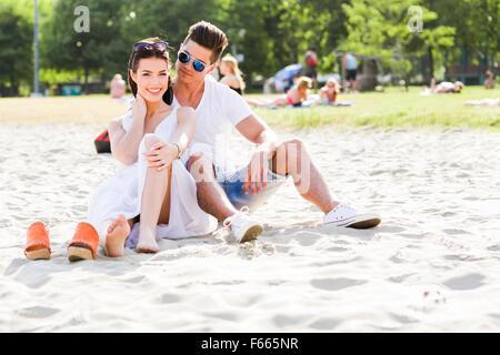 Pareja joven en el amor romántico sentado en una playa de arena y sonriente Foto de stock
