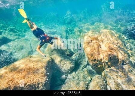 Mujer snorkeling en las aguas turquesas, Punta dei Capriccioli, Costa Esmeralda, Cerdeña, Italia