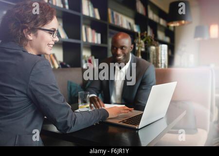 Joven Empresaria mostrando presentación sobre la laptop a su socio de negocios. Feliz ejecutivos en una reunión en el restaurante