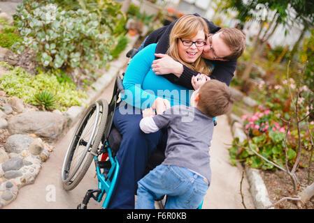 Parapléjicos abrazando a la mujer y la familia en el jardín