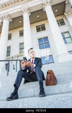 Empresario de raza mixta con teléfono celular en courthouse pasos Foto de stock