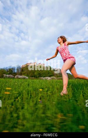 Mujer joven que se ejecuta a través de una pradera, el castillo de Riegersburg en segundo plano, Estiria, Austria Foto de stock