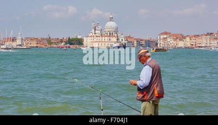 Hombre que pesca en la costa de Venecia con la Basílica di Santa Maria della Salute en el fondo Veneto Italia Europa