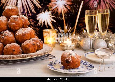 'Oliebollen', repostería tradicional holandés para la Víspera del Año Nuevo. Con champán y fuegos artificiales en el fondo.