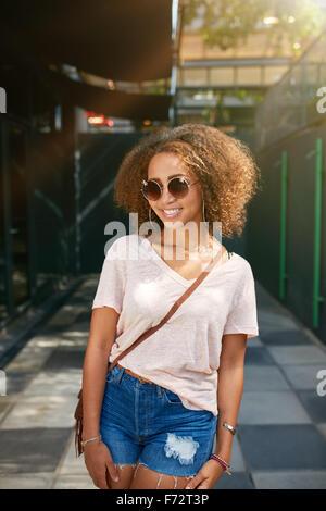 Retrato de una joven y bella mujer negra con gafas de sol sonriente en la cámara. Las hembras jóvenes africanos en casuals posando al aire libre.