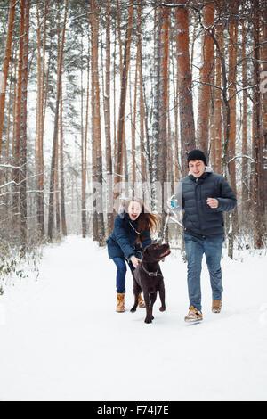 Pareja joven con un perro a divertirse en invierno Bosque en vacaciones. El enfoque selectivo. El estilo de vida de feliz familia moderna. Foto de stock