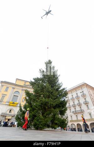 Lugano, Suiza - 20 de noviembre de 2015: Los trabajadores que se desplazan de un árbol de Navidad que se deposita desde un helicóptero
