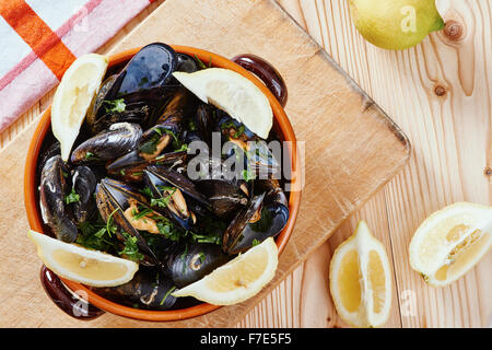 Los mejillones en una olla sobre la placa de corte, limones, mantel sobre mesa de madera