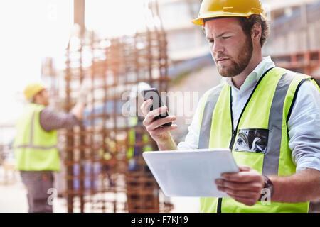 Trabajador de la construcción con la tableta digital de mensajes de texto con teléfono celular en lugar de construcción Foto de stock