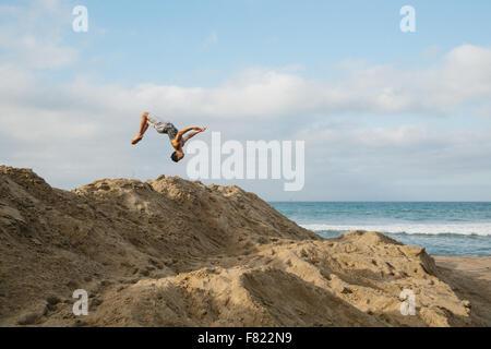 Un hombre joven se voltea sobre dunas de arena en una playa en California