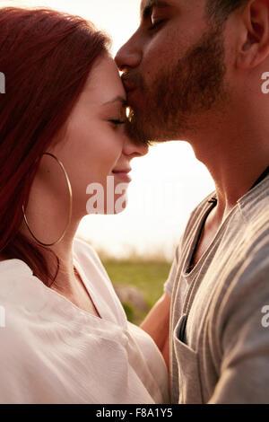 Retrato de joven pareja amorosa junto al aire libre. Joven besar la frente de su novia.