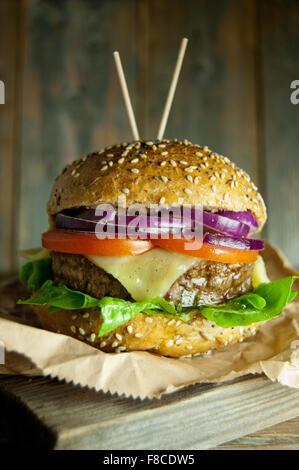 Hamburguesa gourmet con queso fundido, tomate y cebolla relleno en la parte superior de una tabla de cortar de madera Foto de stock