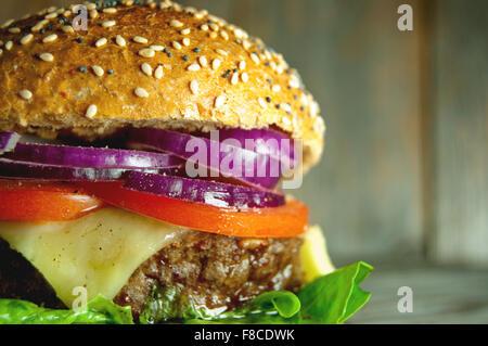 Cerca de una hamburguesa gourmet con queso, tomate y cebolla relleno Foto de stock