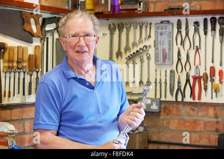 Hombre senior en taller con herramientas permanente