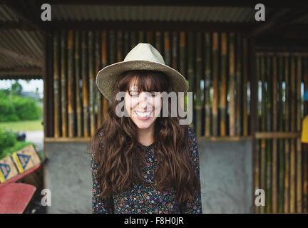 Sonriente mujer caucásica llevar sombrero para el sol al aire libre