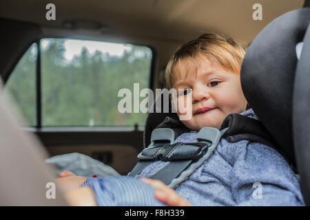 Raza mixta chica sentada en el asiento del coche